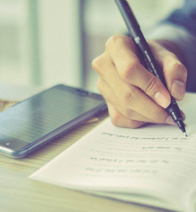 Mensch schreibt auf Notizblock, daneben liegt ein Smartphone: Digitale Medien können Hilfsmittel im Unterricht sein.