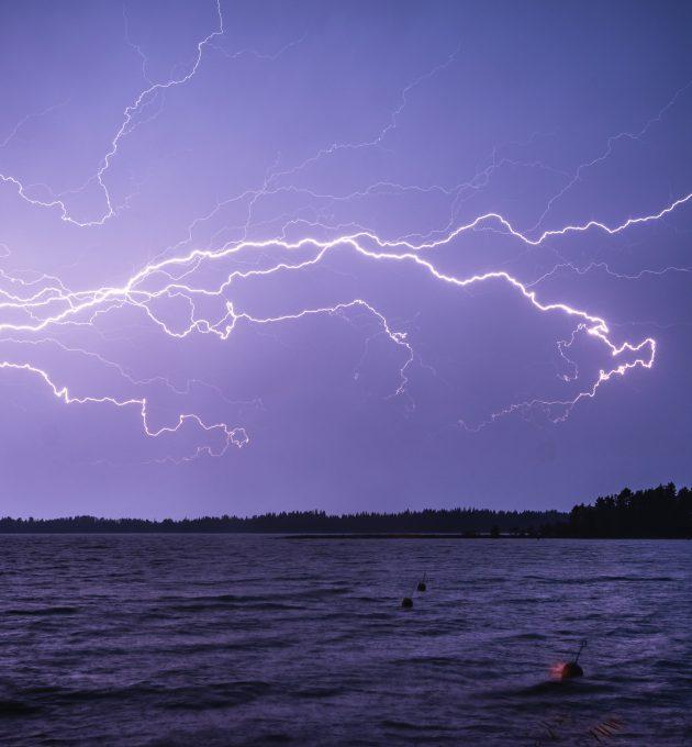 Blitzeinschlag über einem See. Unwetter und Extremwetterereignisse werden im Zuge der Klimakrise zunehmen.